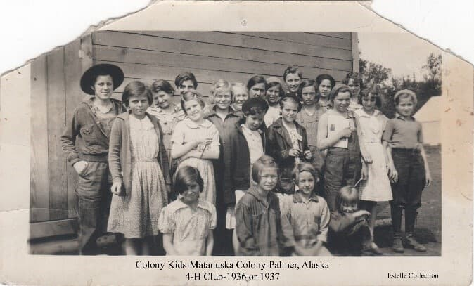 """Image shows a group of young girls standing together in front of a wooden building. The group is identified as """"Colony Kids"""" making up a 4-H Club. A white tent is visible in the background. One adult, identified as Mrs. Ring, is in the back row, center. Some others are identified as: Genevieve Ring, June Lentz, Jean Mae Sandvik, June France Leila Peterson, Lucille Ring, Jean Kindgren, Pat Hemmer, and Pat Ring."""