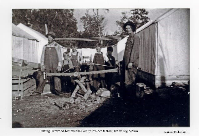 Image is of two men standing next to a cross-cut saw embedded in a log sitting atop a sawbuck with several cut lengths of firewood on the ground. Several boys are behind them, two holding axes. They all stand between two rows of colony tents with clothes hanging on lines behind them and trees beyond.