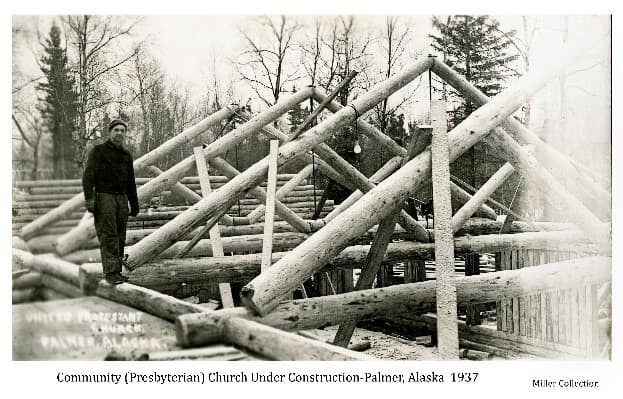 Image shows a man standing on a log wall beside several peeled log rafters with log walls behind and below. Various boards lean against the rafters and a power cord with a light bulb hangs from one rafter. The structure under construction is identified as the Community (Presbyterian) Church of Palmer. There is evidence of light snow cover and the man is warmly dressed. Tress form the backdrop.