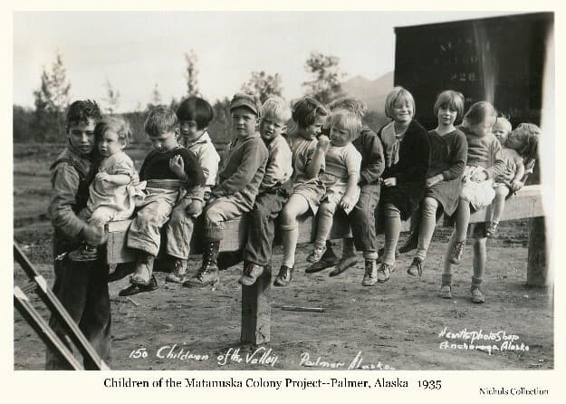 Image shows a group of small children sitting on a rail in front of a rail car. Trees and mountains are visible in background.