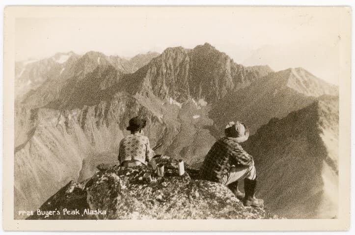 """Summer view of two people perched atop a rock facing away from the camera toward rugged mountains to the south. Two cans and a water bottle on the rock suggest a repast.  Prominent is the mountain known at the time as Beyer's Peak, latter shown on maps as Matanuska Peak.  While the name on the photo is spelled """"Buyer's"""", research indicates that the name originated in reference to Herman Edward Beyer, thought to be the first person documented to have climbed the peak in 1942."""