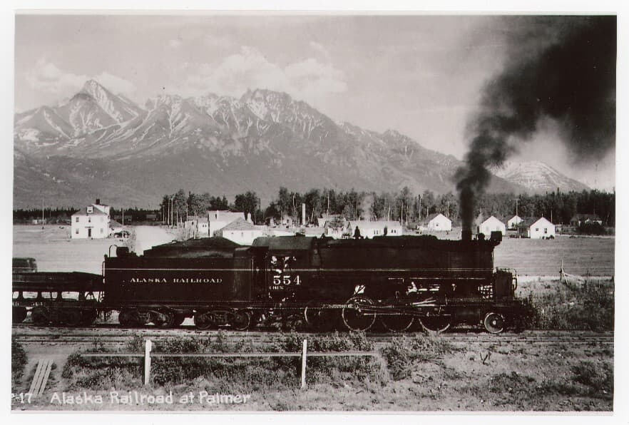 """Image is of Alaska Railroad engine #554, blowing black smoke, on tracks in central Palmer with ARRC staff housing and the """"Dorm"""" in middle ground beyond.  Forest and mountains in background."""