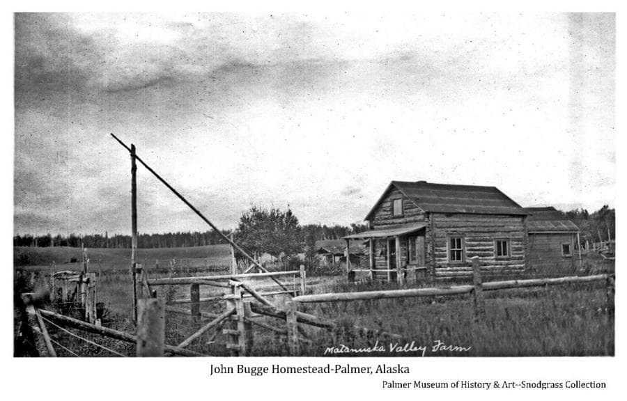 Image shows pole fencing and large wood pole gate in near foreground, a log cabin with a frame addition behind in mid-foreground, another small log cabin in middle ground with fields and forest beyond.