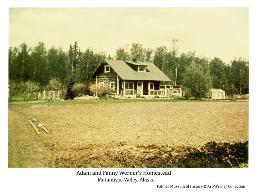 Image is a color summer color view of Adam Werner's house with tilled field in front.