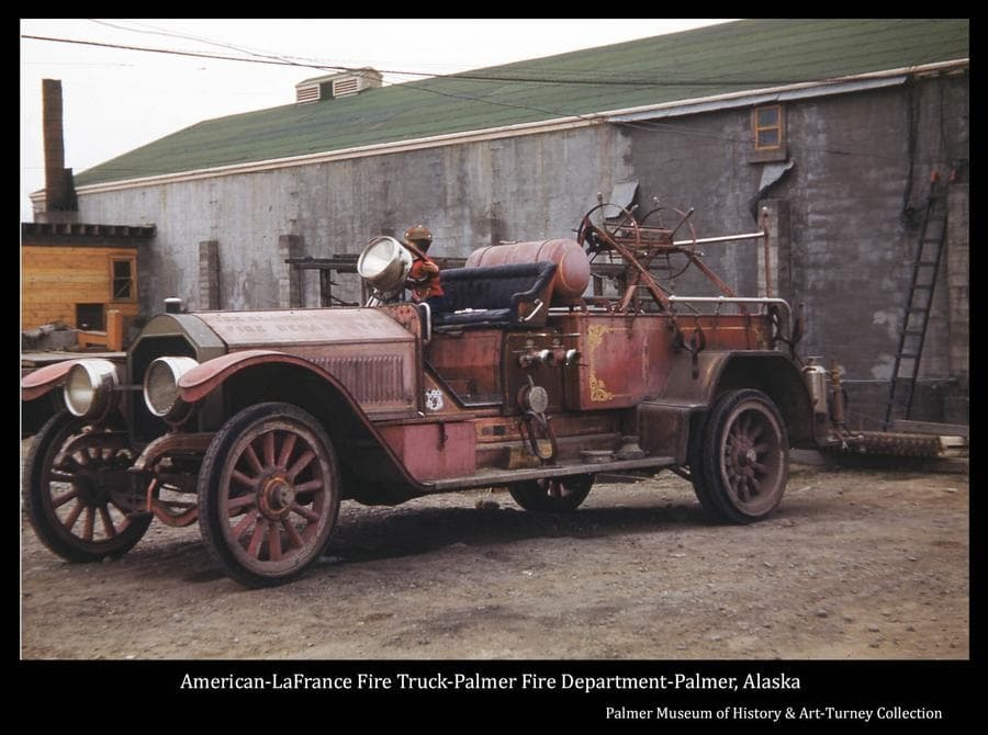 """Image is of a vintage American-LaFrance fire truck parked on the west side of the Palmer theater building.  A child is visible on the seat at the steering wheel, his trusty cap pistol ready at hand on the seat beside him.   """"ALASKA RAILROAD FIRE DEPARTMENT"""" is stamped on the engine hood, and a U.S. Federal property decal, visible on the side of the foot rest, is a reminder that at the time this truck was part of the railroad fleet, that railroad was still owned and operated by the federal government.  Various information indicates the model year of this truck as 1909 or 1916.  Other photos in our collection show this truck at the Lazy Mountain Children's Home.  Further research is needed to identify the truck's history, age and current status."""