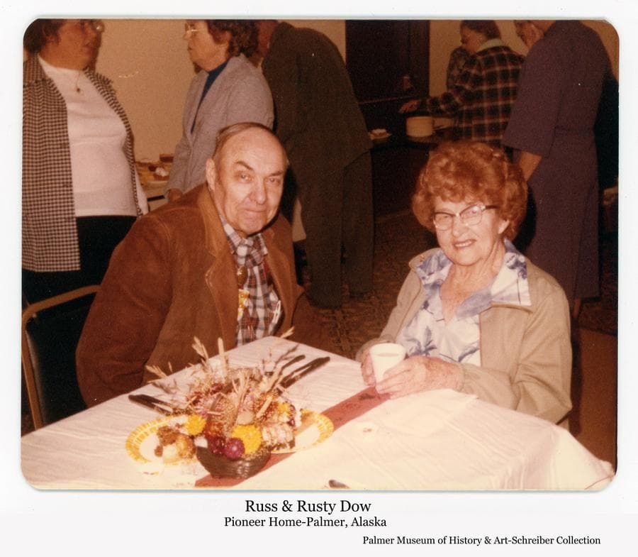 Image is of Russell (Russ) Dow and his wife Rusty at a dinner at the Palmer Pioneer Home.  Russ was a well-known photographer and historian.  Rusty was a well-known artist and truck driver throughout the Valley and beyond.