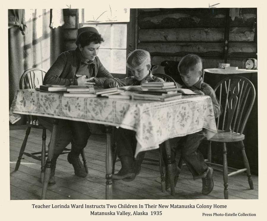 This is a slightly enhanced press photo.  Image shows teacher Lorinda Ward seated at a kitchen table piled with books and two small boys seated next to her doing their school work.  The boys are not identified.  The setting is in a newly-constructed Colony log home.