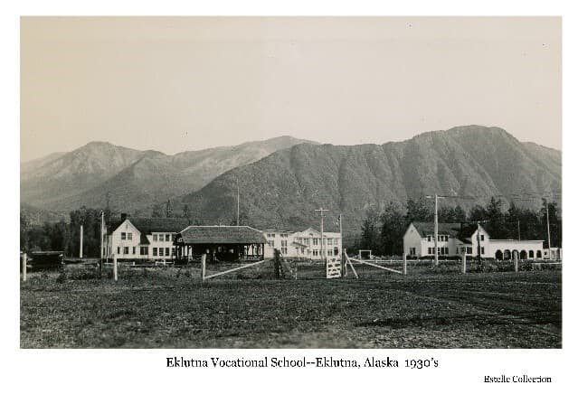 Image shows large white buildings of the Eklutna Vocational School in middle ground. A wire fence with wooden gate is in foreground, railroad tracks and depot building just beyond. Forest and mountains in background. Power poles and lines are evident.
