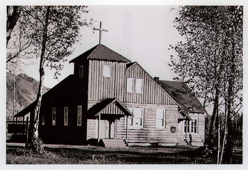 Image is of the front (west side) of the Palmer Lutheran log church with birch trees in foreground and a mountain beyond. A sign is visible in the left foreground and a plaque is visible on the church wall.