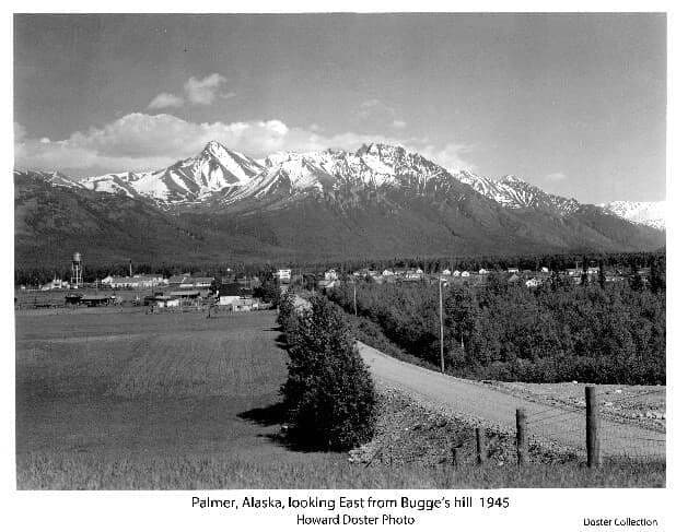 Image is an easterly view of a gravel road in foreground, identified as the Palmer-Wasilla Road, beside an open field and buildings on the left, identified as John Bugge's homestead. Buildings of the town of Palmer are evident in middle ground with many identifiable, including the water tower. Snow-capped mountains are in background with clouds above.