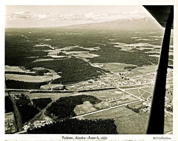 Image is an oblique aerial view looking northwest across the Matanuska Valley with the City of Palmer in foreground. The fairgrounds and surrounding farms are evident. The Glenn Highway passing through Palmer, and the Palmer-Wasilla Road are evident. Land clearing patterns are apparent. Talkeetna Mountains are in background.