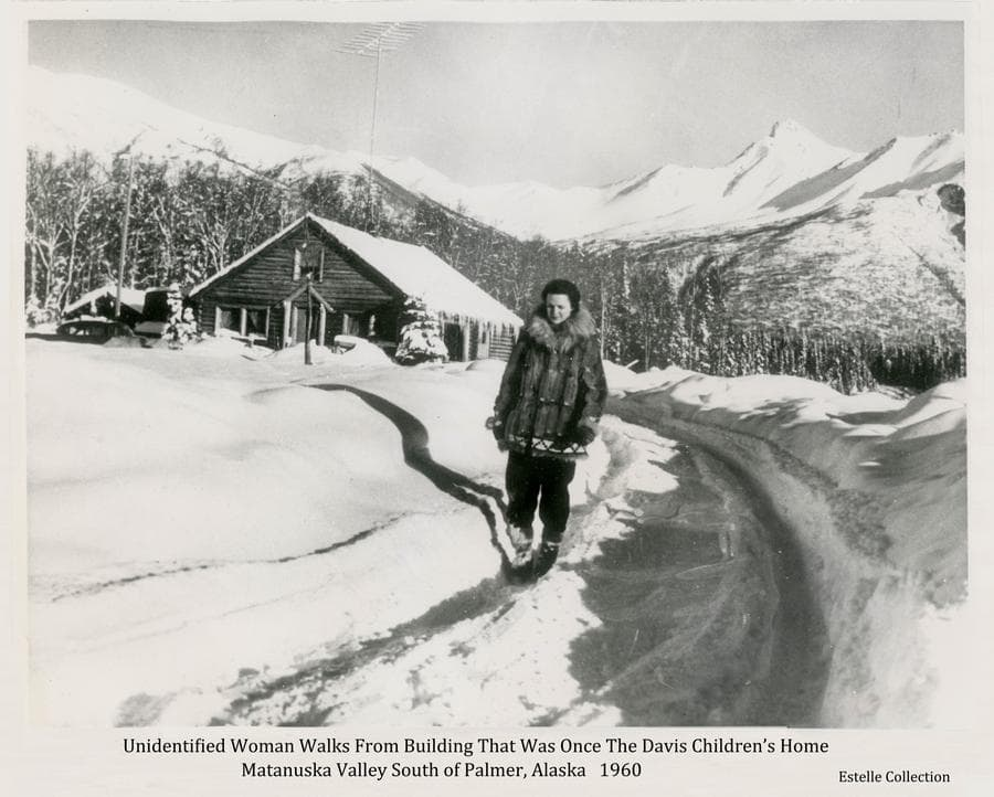Image shows a winter scene of an unidentified woman clad in a fur parka walking in the driveway of a large log house.  Deep snow is evident.  Snow-clad mountains are in background.  The house was once the site of the Davis Children's Home.