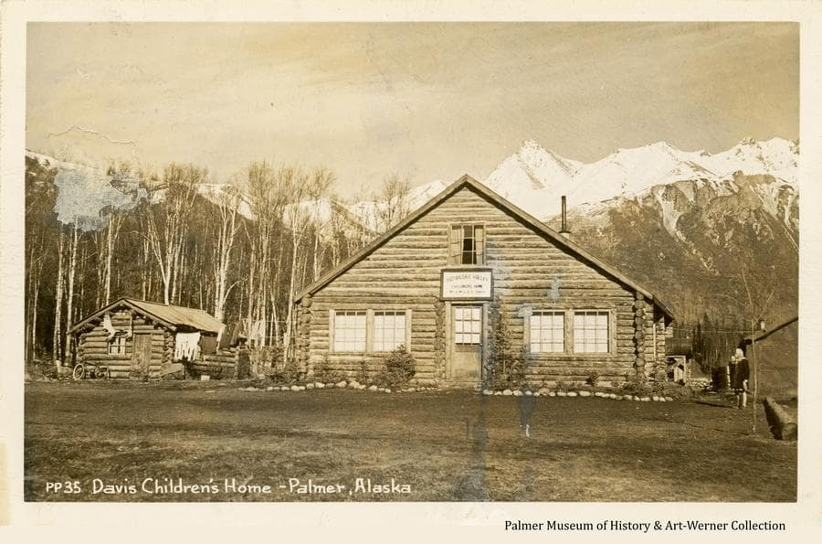 """Image shows a large log house with a sign over the front entry door identifying it as """"Matanuska Valley Children's Home, Mr. & Mrs. S.L. Davis""""  At left is a smaller log building with moose horns on the wall, a bicycle in front and washing hanging on the line.  A woman stands to the right of the large building.  Another smaller building is partially visible at right.  Birch trees are evident behind the buildings.  Snow-clad mountains dominate the background."""