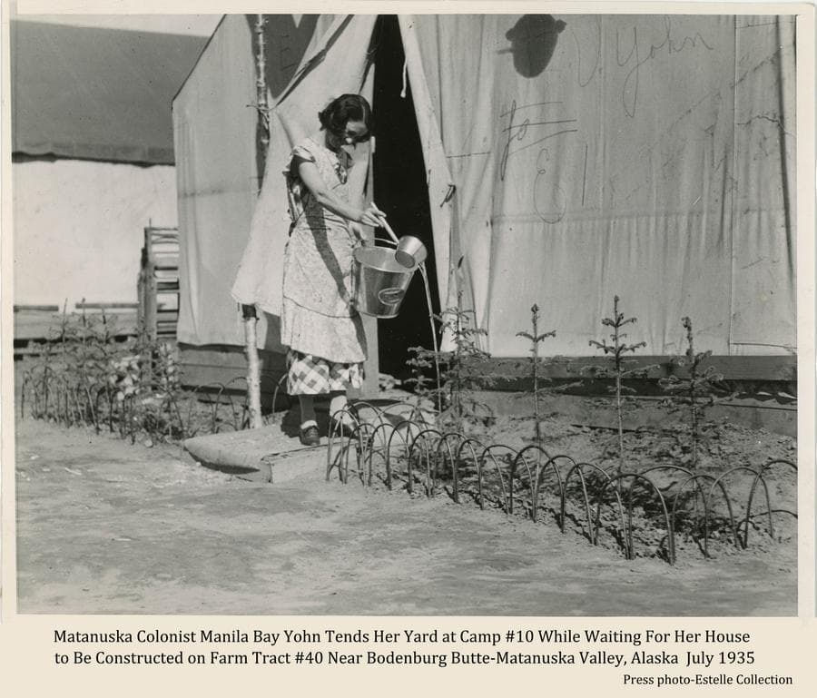 Image shows a young woman, identified as Colonist Manila Bay Yohn, watering her small spruce trees and strawberries planted in front of her temporary tent home.  Her tent is prominent behind her and another tent is visible beyond.