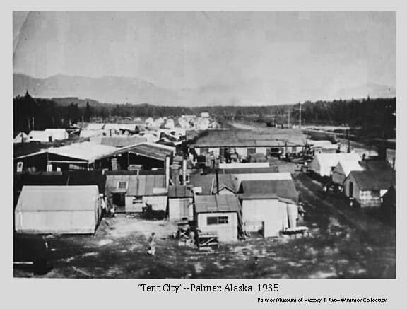 Image is a north-facing view of tents and small buildings that served the Matanuska Colonists at Palmer during the early summer of 1935. A person is visible in foreground, forest in middle ground and mountains are visible in background.