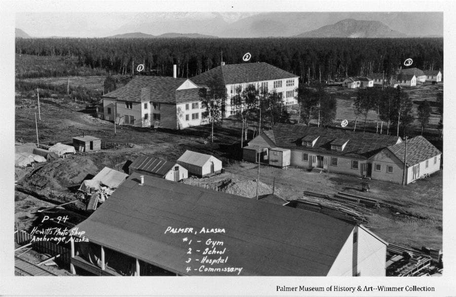 Image is a summer oblique view of newly-constructed Palmer community center buildings including the Gym, School, Hospital, Commissary/Trading Post, and Warehouse. Buildings are numbered and identified. Temporary tents and lumber piles are apparent. Heavy forest is behind the buildings and Bodenburg Butte is visible in background.
