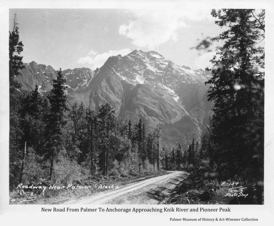 Image is of a lane-and-a-half gravel road through heavy spruce forest in the direction of a prominent mountain, identified as Pioneer Peak.  This is the newly constructed road from Palmer that connected the Matanuska Valley to Anchorage after the Knik River bridge was completed in September of 1936.  The location shown is in the vicinity of Bodenburg Butte as the road approaches the Knik River.