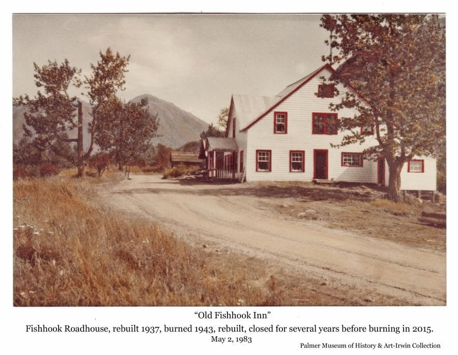 """Image shows a large three story wooden building identified as the """"Fishhook Inn"""" with a gravel road in front, a small building behind and a mountain in background. The first Roadhouse/ Inn at this site on the road up to the Hatcher Pass gold mines is thought to have been constructed in 1916.  It apparently burned or was torn down in fall of 1937 when it was re-built and operated as the """"Little Su Roadhouse"""" until 1942.  Burning again in 1943, it was re-built and expanded, operating as the """"Mother Load Lodge"""" until several years prior to 2015 when the empty structure was destroyed by fire once more."""