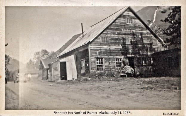 """Image shows a large building identified as the """"Fishhook Inn"""" with a mountain behind it, a dirt road in front with an indistinct car, people, and another building in background."""