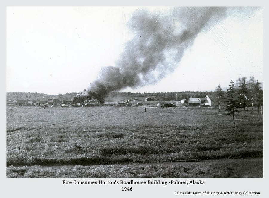 Image is a view across the Community Center quad, west toward the commercial center buildings of Palmer as a large column of smoke rises from Horton's Roadhouse as it burned in 1946. Numerous people and vehicles are visible.  Also destroyed besides Horton's Roadhouse, or apartments, were Horton's Cafe, the Frontier Bar and the Frontier Liquor Store.