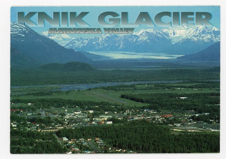 Image is an oblique southeasterly summer view across Palmer and the Matanuska River to Knik Glacier and snow-clad mountains beyond.