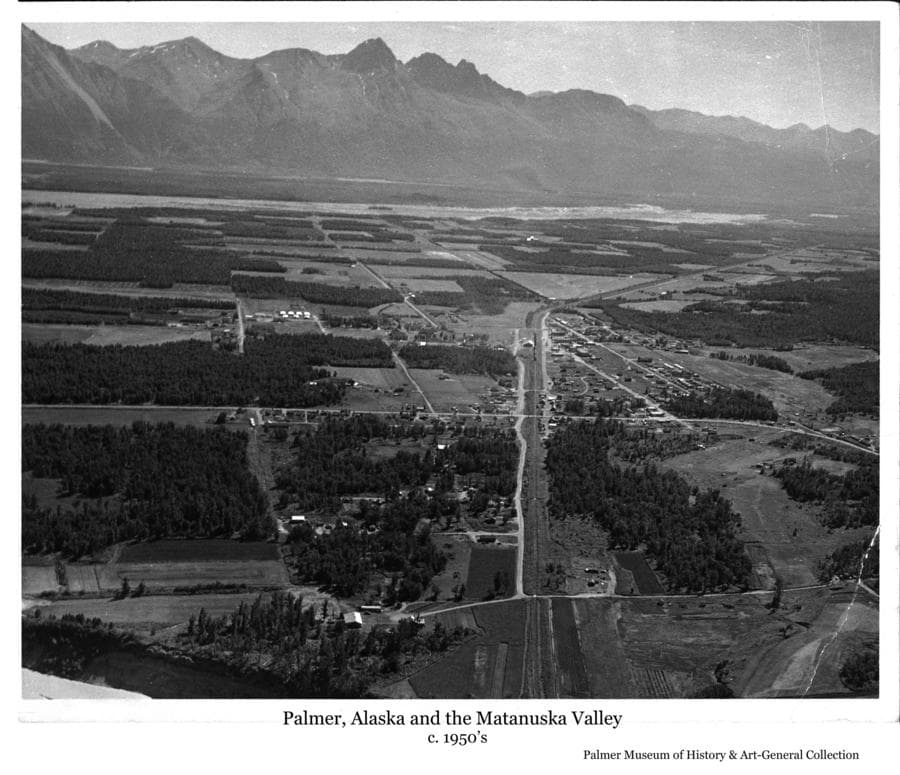 Image is an oblique aerial summer view from above the Matanuska River looking south over Palmer and the surrounding area to the Matanuska River and the Chugach Mountains beyond.