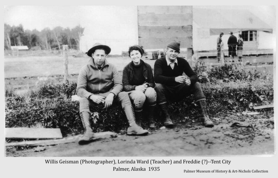 Image shows three people sitting in foreground, identified as: Willis T. Geisman (official Colony photographer) at left; Lorinda Ward (school teacher) center; and Freddie.  Other people are evident in middle ground standing in front of a tent.  Heavy forest is in background.