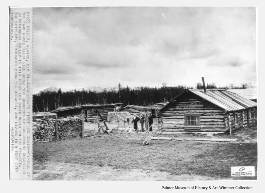 """This is a press photo issued to newspapers back in the States from the early days of the Matanuska Colony project.  Information sent along with the photo is attached at left, and reads: """" PALMER, ALASKA, MAY 24—MATANUSKA'S FIRST LOG CABIN—Typical of the farm homes that will house the hundreds of government colonists in Matanuska Valley is this first log cabin built on the project.  The settlers, emigrants from the Midwest, are living in a tent city temporarily.""""  More typical than the future Colonist's homes, (these are actually a long-established homesteader's cabins located in what would become downtown Palmer) is the misinformation this text represents that was so often received by folks """"back home""""."""