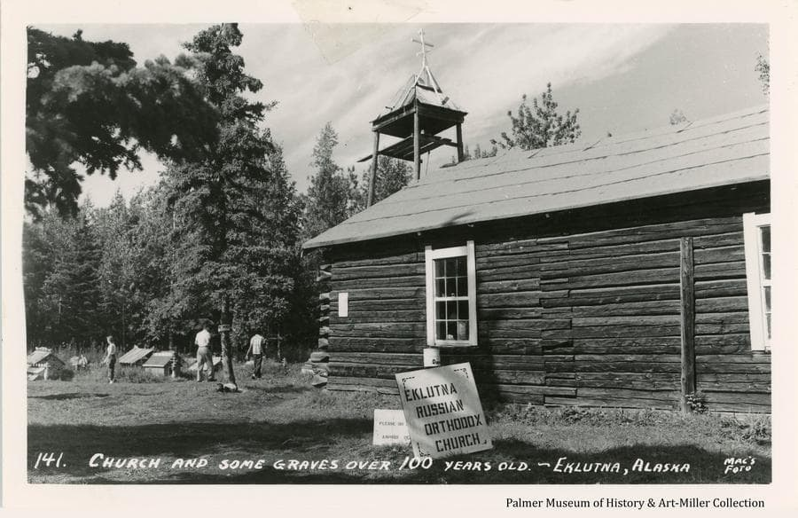 Image is a three quarter side view of the Eklutna Russian Orthodox Church in the foreground.  Identity and instruction signs are in near foreground.  People are walking among grave houses in middle ground with trees beyond.