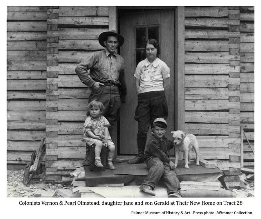 Image is of Colonists Vernon and Pearl Olmstead with their children Jane and Gerald, and the family dog, in front of their new log home located on tract #28 near the Matanuska Experiment Farm.  They were reported to be the first Colonists to move from their tents into their new home in 1935.  The squared logs used in construction were milled at a sawmill set up not far away near Camp 2.