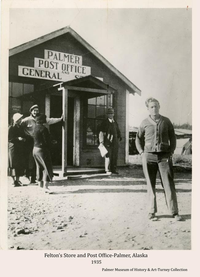 """This is a press photo showing people standing at the front of Felton's store and Post Office.  James Felton and partner, Ward, operated the Post Office with the community name of """"Warton"""" until 1935 when the name was changed to """"Palmer"""".  Accompanying information identifies the young man in front as John Walsh, a university graduate, employed as a carpenter, probably as one of the Matanuska Colony project transient labor force."""