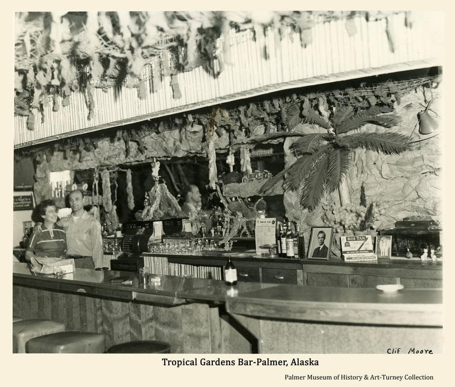 Image is an interior view of the Tropical Gardens Bar in Palmer.  Ruby and Bill Miller, proprietors from 1959 until 1962, are standing behind the bar at left.