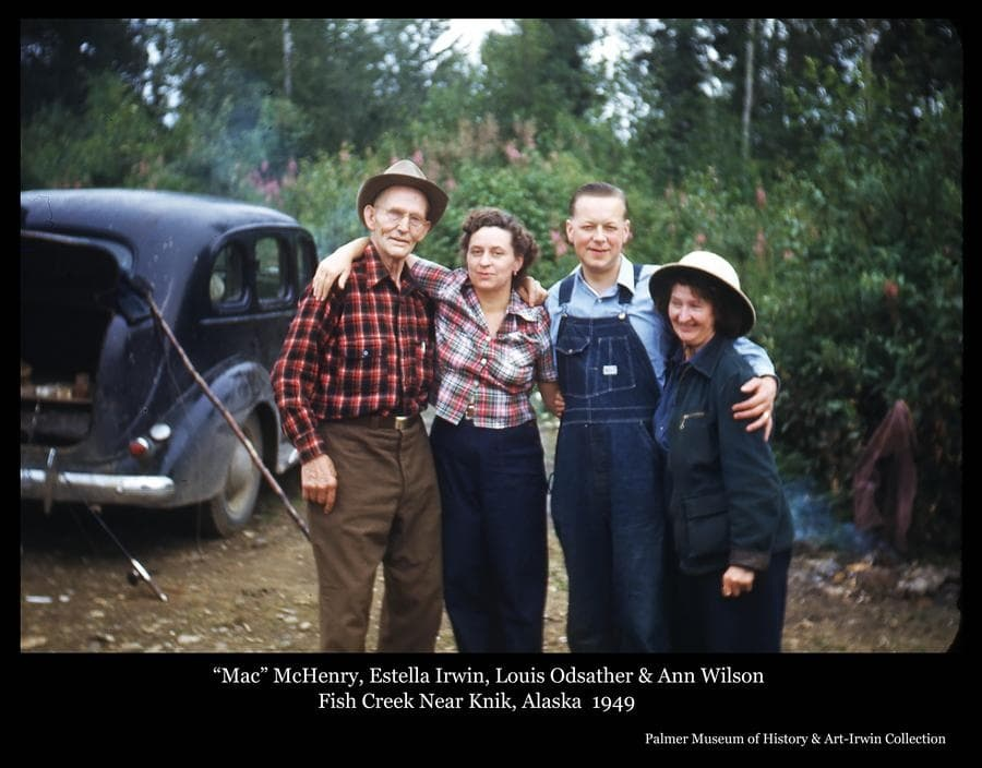 """Photo is a color image of four people, identified as homesteader """"Mac"""" McHenry, Estella Irwin, Louis Odsather and homesteader Ann Wilson.   A black automobile is behind and fishing gear is evident.  The photo was taken at Fish Creek near Knik, Alaska."""