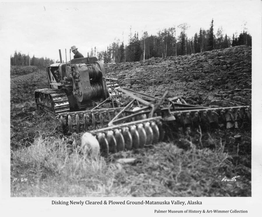 Image is of a man on a cat tractor pulling a disk on newly broken and plowed ground.  The hillside beyond has been plowed with heavy forest at the ridge top.