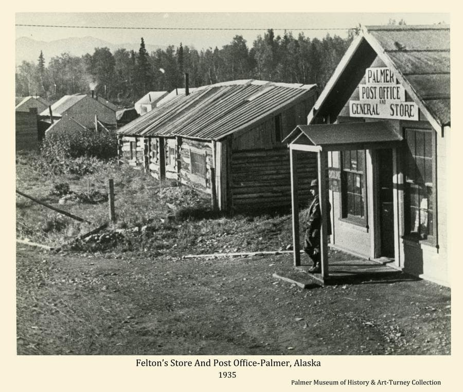 """Image shows a man standing on the porch of Felton's store and post office in foreground.  A large log cabin is in near middle ground with several Colony tents visible beyond.  Heavy forest is the backdrop with mountains faintly visible in background.  Location is the former homestead of Georen O. White reflected by the large log structure.  Felton and partner, Ward, acquired the property and operated the Post Office with the community name of """"Warton"""" until 1935 when the name was changed to """"Palmer"""".  The Matanuska Colony """"Tent City"""" temporarily occupied part of the property."""