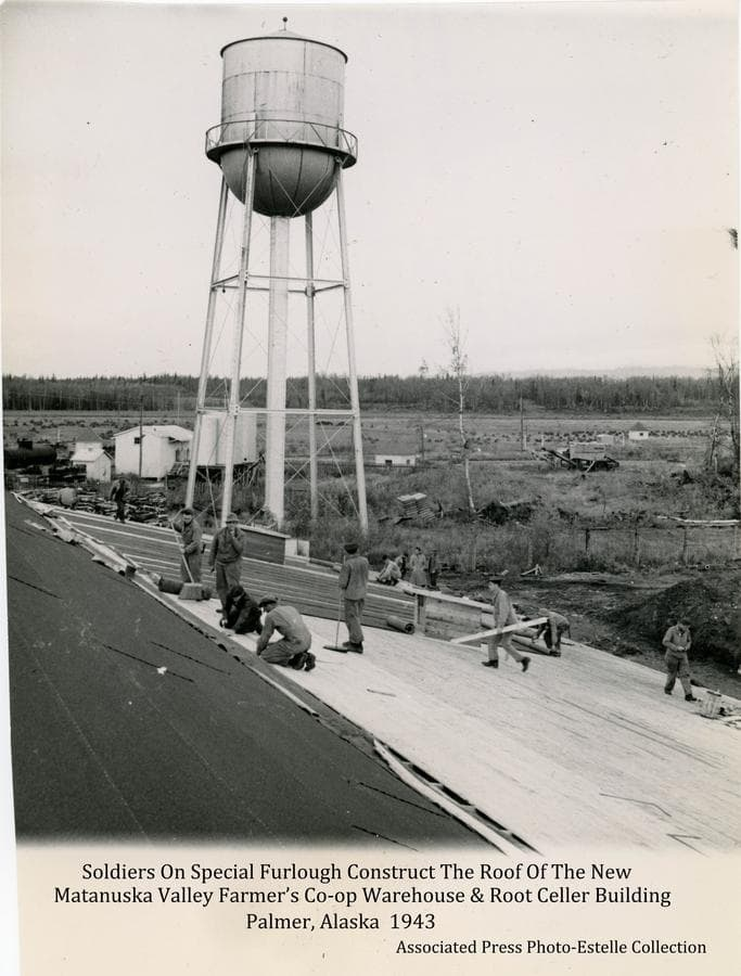 Image shows several soldiers preparing the roof of a large building for installation of roofing paper.  The building is an additional warehouse facility at the Farmer's Matanuska Co-op.  The Palmer water tower is prominent in middle ground, with fuel storage tanks, a small building and a railroad tank car adjacent.  Two pump houses on the water supply line from the north are visible in middle ground, as is a large unidentified machine.  In far middle ground is a field with many small hay stacks backed by heavy forest. Mountains are faintly visible in background.