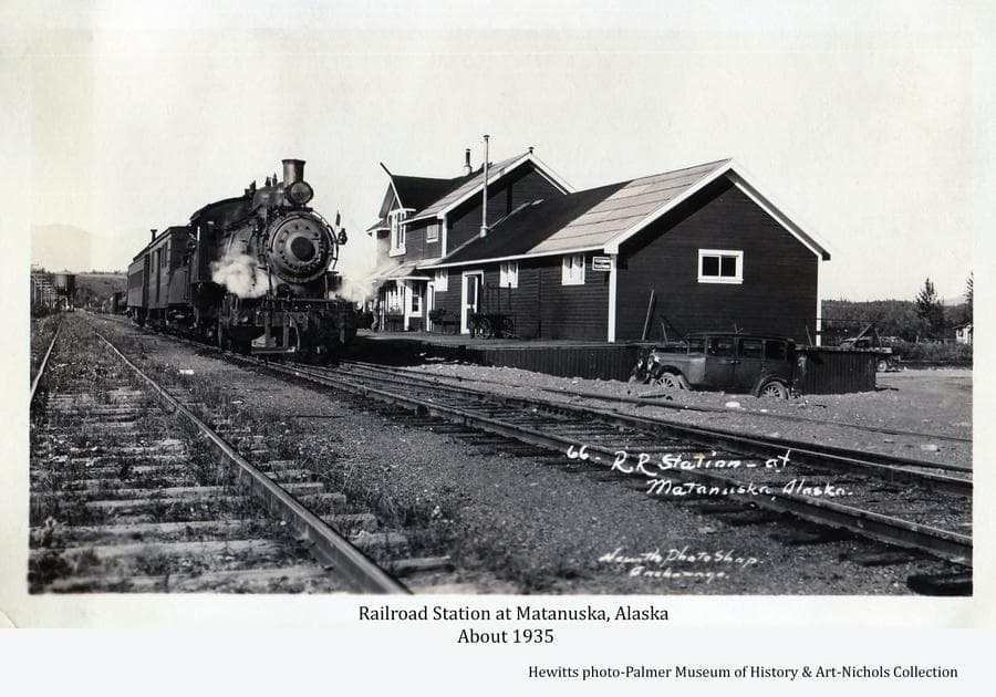 Image shows railroad tracks in foreground with a steam engine and the Matanuska depot in middle ground.  Two automobiles are evident.  A man is visible walking into the building and another man is evident in the cab of the engine.  A water tower is visible in the background with trees beyond.