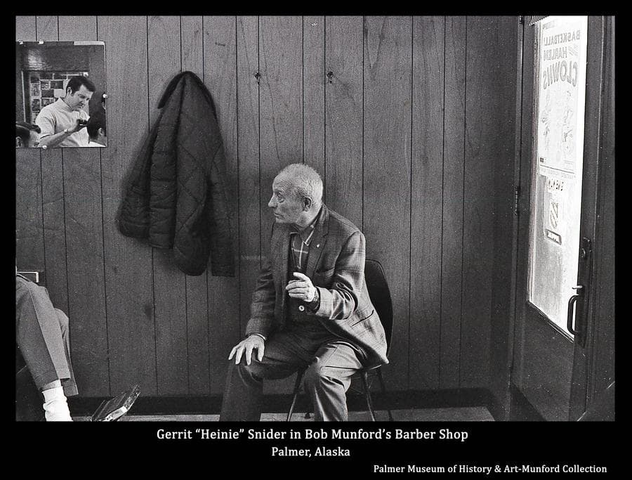 """Image is of Gerrit """"Heinie"""" Snider seated in Bob's Barber Shop in the Wright building in Palmer.  Bob Munford is seen in a mirror on the wall as he cuts the hair of a patron.  An ad posted on the shop door advertises an up-coming basketball game of the """"Harlem Clowns""""."""