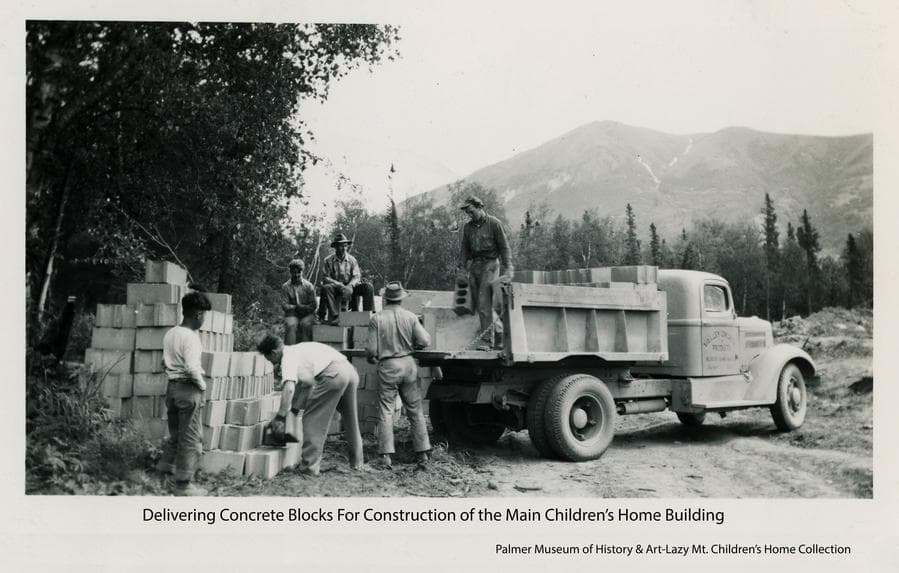 """Image shows several men unloading concrete blocks from a truck and stacking them on the ground.  """"Valley Concrete Products"""" is painted on the door of the truck.  Heavy forest is at left and middle ground with Lazy Mountain in background."""