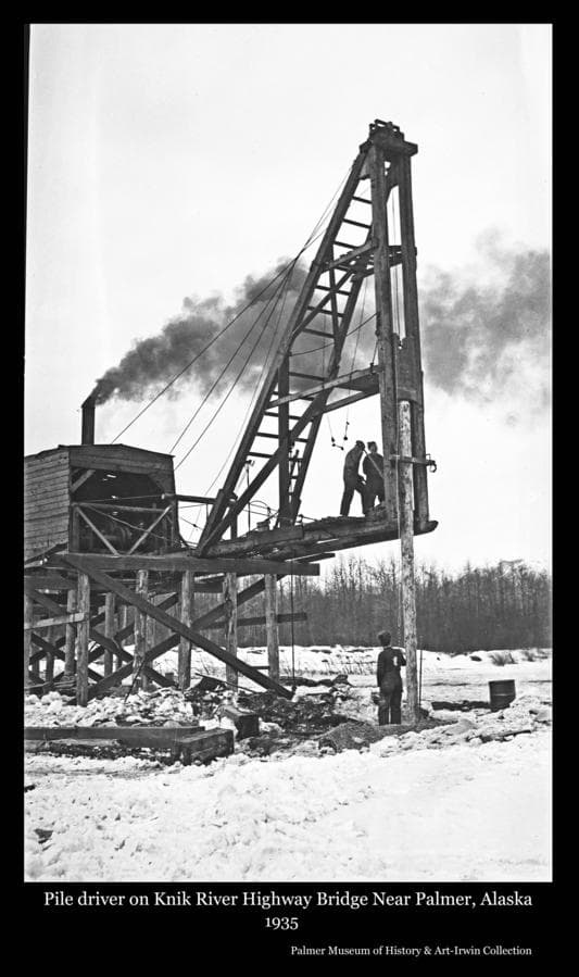 Image shows a winter view of men operating a pile driver placing timbers for construction of a highway bridge over the Knik River to connect the road between Palmer and Anchorage