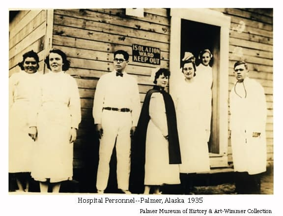 Image shows several nurses, including Max Sherrod (third from left) and Dorothy Sherrod (fifth from left), and Dr. Albrect at right.  They are standing in front of the temporary hospital isolation ward building established in Palmer before the new community hospital was opened in fall of 1935.