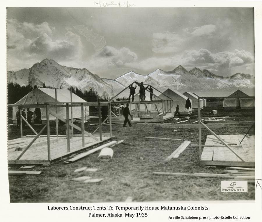 This is a slightly enhanced press photo.  Image shows transient laborers constructing tents to house arriving Matanuska Colonists at the Palmer town site.  Two tent platforms are in foreground, men are constructing a tent frame in middle ground with several completed tents nearby.  Snow-clad mountains are in background under scattered clouds.