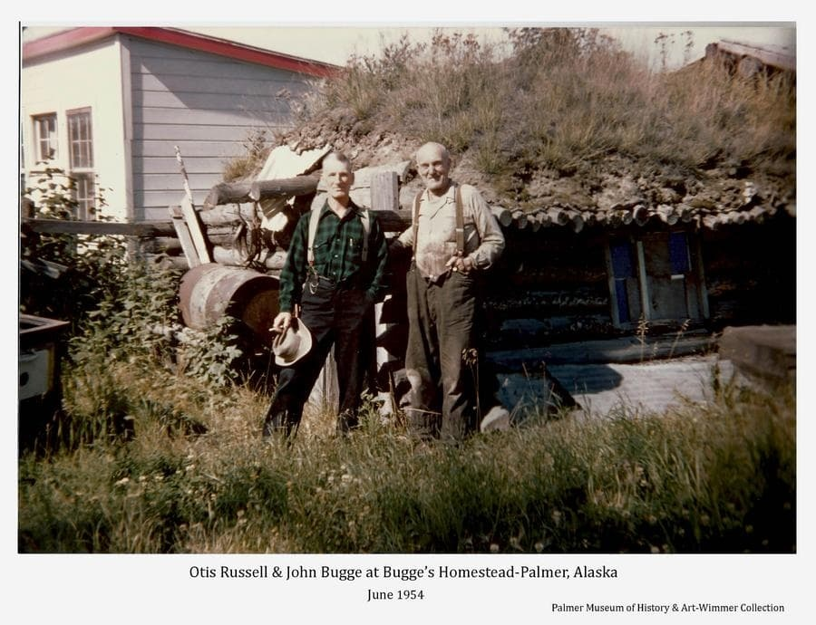Color image of two men, identified as Otis Russell (left) and homesteader John Bugge, standing in front of one of the log cabins on Bugge's homestead at Palmer, Alaska.   A modern frame building is partially visible behind.