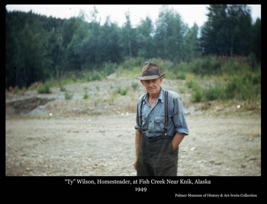 """Photo is a color image of a man, identified as homesteader """"Ty"""" Wilson standing in a gravel area with trees behind."""