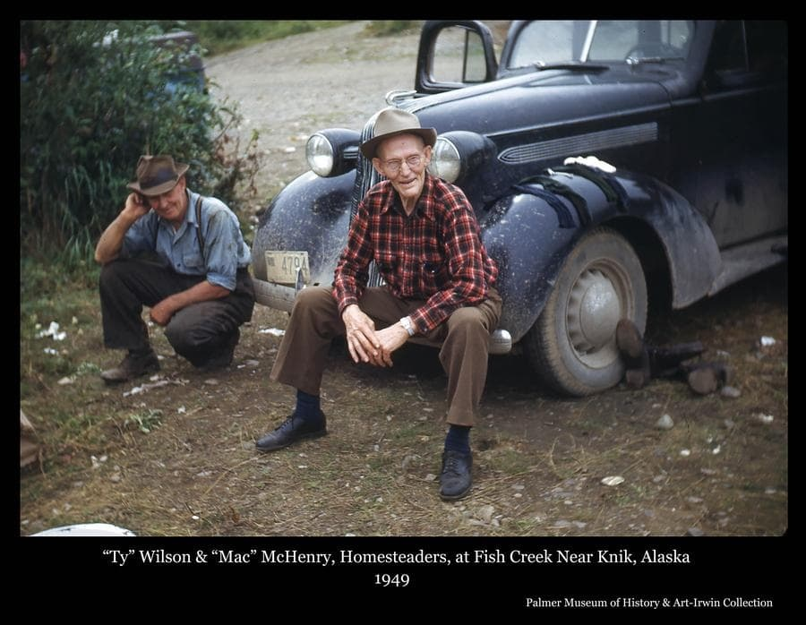 """Photo is a color image of two men, identified as homesteaders """"Ty"""" Wilson and """"Mac"""" McHenry at the front of a black automobile.  Both men homesteaded in the Fairview Loop area south of Wasilla, Alaska.  The photo was taken at Fish Creek near Knik, Alaska. Wet socks and boots in the photo may indicate they had been  fishing."""