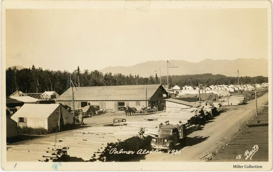 """Image is a northwesterly view taken from atop a railroad car showing considerable """"Tent City"""" activity.  A truck is parked alongside the road in foreground with men loading lumber from a large pile.  Other men and automobiles are evident as is a horse-drawn wagon with people in the wagon.  A tent is in foreground at left and a large frame building is at center in near middle ground.  Piles of tarp-draped material are scattered about.  Many tents are visible in background with heavy forest and mountains beyond."""