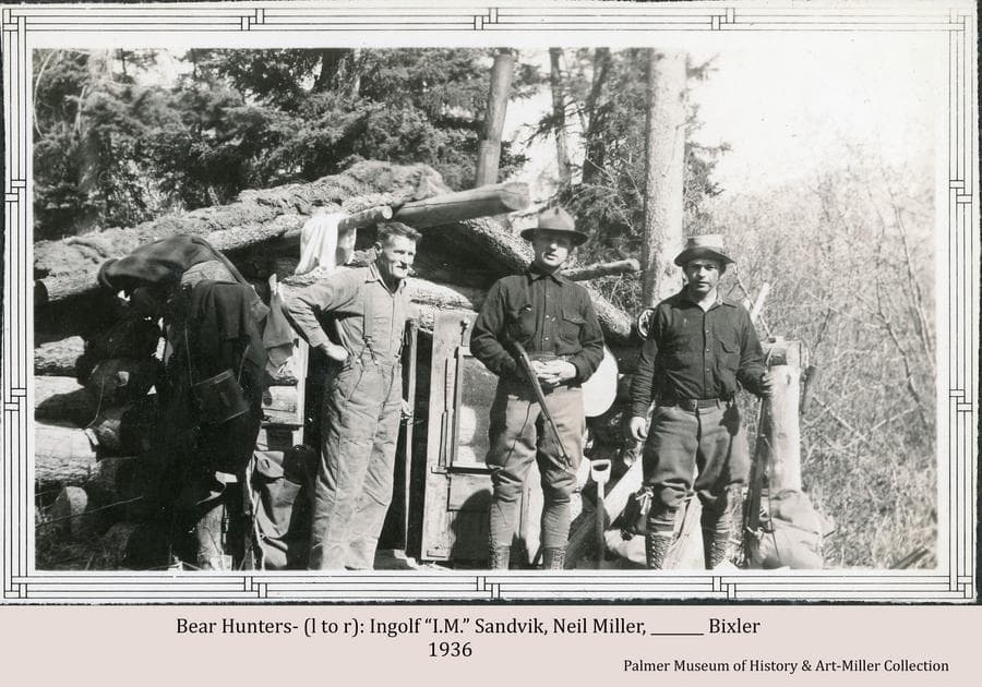 """Three men, identified as Ingolf """"I.M."""" Sandvik (left), Neil Miller (center), and Bixler (right), stand in front of a small, sod-roofed log cabin.  Miller and Bixler are holding rifles.  Large trees and brush form the background.  Notes associated with the image indicate the men are on a bear hunt."""
