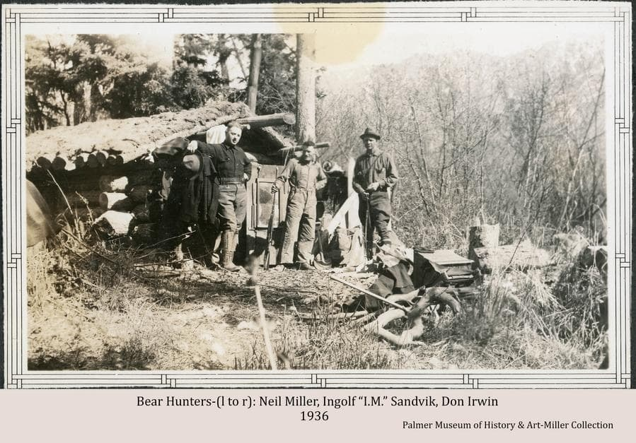 """Image shows three men, identified as Neil Miller (left), Ingolf """"I.M."""" Sandvik (center), and Don Irwin (right), standing in front of a small sod-roofed log cabin. Sandvik and Irwin are holding rifles.  Large trees and brush form the background.  Notes associated with the image indicate the men are on a bear hunt."""