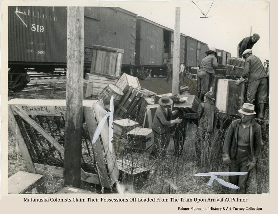 This is a slightly enhanced news photo showing Matanuska Colonists sorting through the boxes, barrels, trunks and crates of possessions off-loaded from the train at Palmer and stacked along the tracks, claiming their own and loading them on a truck to be delivered to their tents.  The marks on the photo indicate how it would be cropped for printing in the newspaper.