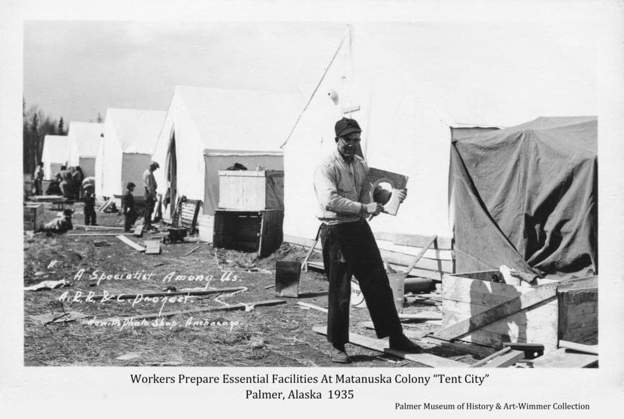 """Image shows a man putting finishing touches on the seat to be installed in one of the """"outhouses"""" established for the Colonists.   Other people are visible in background.  The setting is amongst tents, wooden crates and other material of the early stages of establishing life in the Colony temporary """"Tent City""""."""